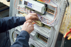 Technician assembling low voltage assembling industrial HVAC control panel in workshop. Close-up photo of the hands.