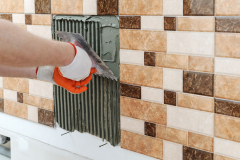A tile's hand is holding a notched trowel.